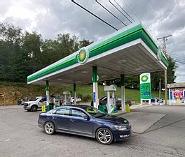 Green and white gas station sign